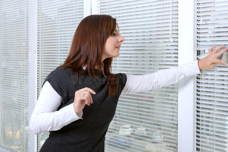 Flicka som kikar till och med fönsterrullgardiner på gatan royaltyfria bilder