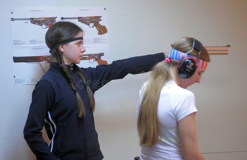 Flicka som konkurrerar, i att skjuta en pistol arkivfoto