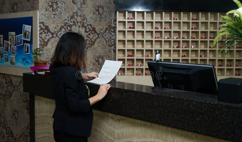 Flicka som kontrollerar i hotell på mottagandeskrivbordet royaltyfri bild