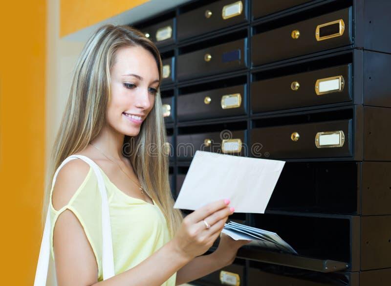 Flicka som kontrollerar upp brevlådan royaltyfria bilder