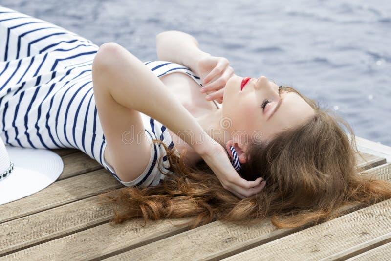 Flicka som kopplar av på bryggan nära havet fotografering för bildbyråer