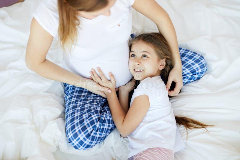 Flicka som kramar den gravida mamman arkivbilder