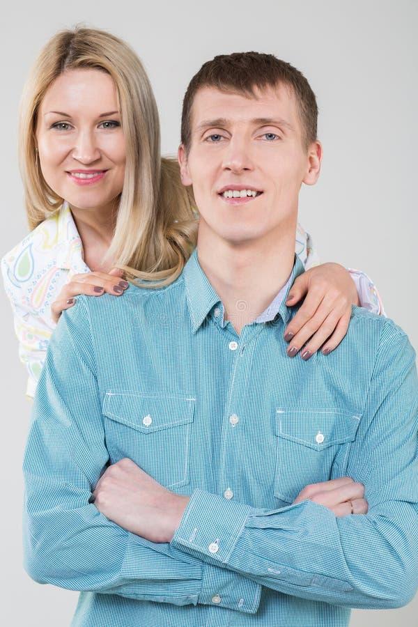 Flicka som kramar den gulliga mannen i skjorta i studion fotografering för bildbyråer