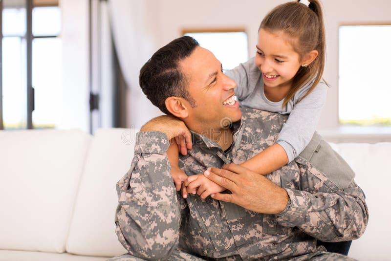Flicka som kramar den militära fadern royaltyfria bilder