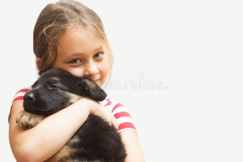 flicka som kramar den små valpen royaltyfri bild