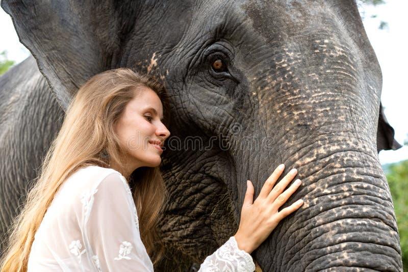 Flicka som kramar en elefant i djungeln royaltyfri foto