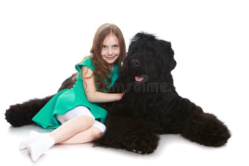 Flicka som kramar en hund arkivfoton