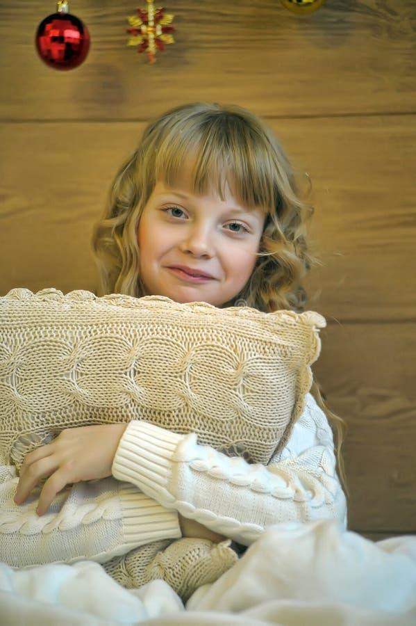 Flicka som kramar en kudde arkivfoto