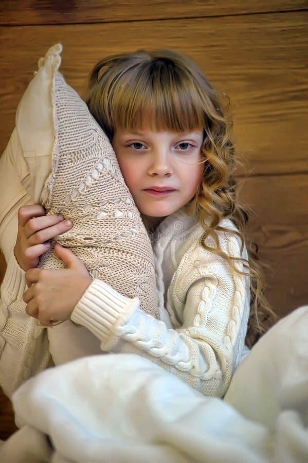 Flicka som kramar en kudde arkivfoton