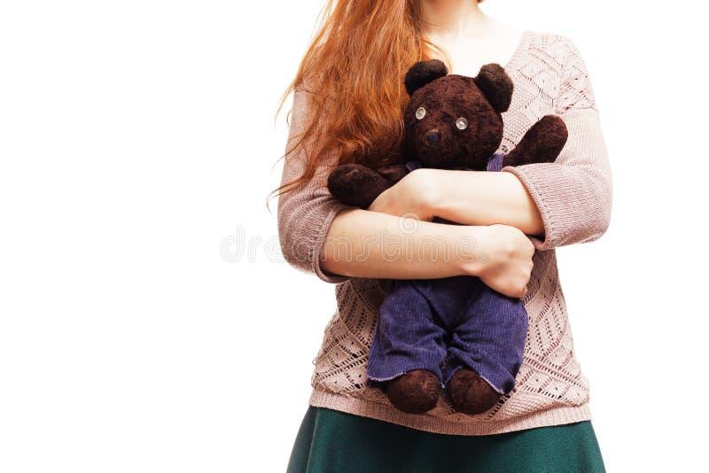 Flicka som kramar hennes favorit- nallebjörn arkivbild