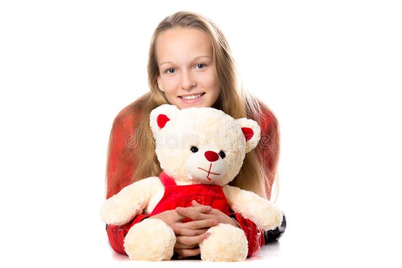 Flicka som kramar leksaken royaltyfri fotografi