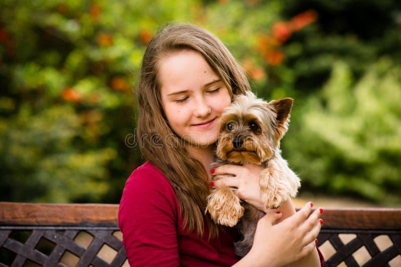 Flicka som kramar med hennes hund arkivbilder