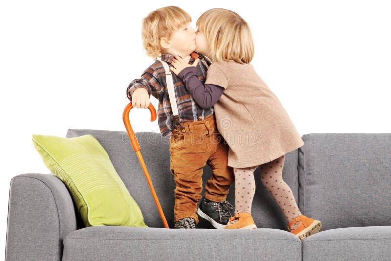 Flicka som kysser en pojke, medan stå på en modern soffa arkivfoton