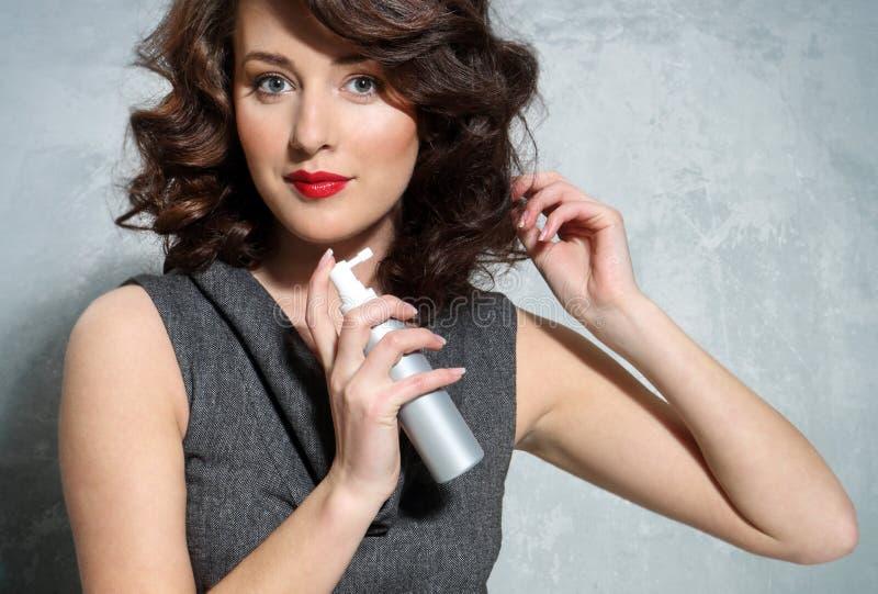 Flicka som lägger knipor genom att använda hårspray arkivbilder