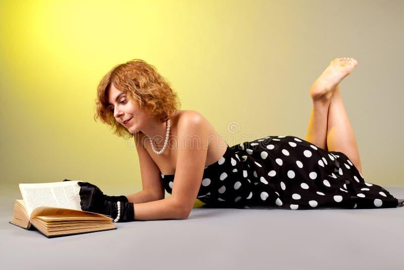 Flicka som lägger medan läsebok arkivbild