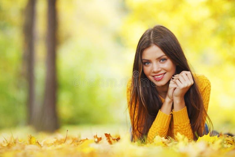 Flicka som lägger på höstblad royaltyfri foto