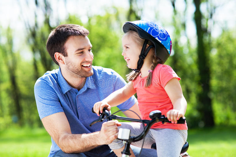 Flicka som lär att rida en cykel med hennes fader royaltyfria foton