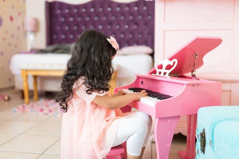 Flicka som lär att spela det lilla pianot hemma arkivbilder