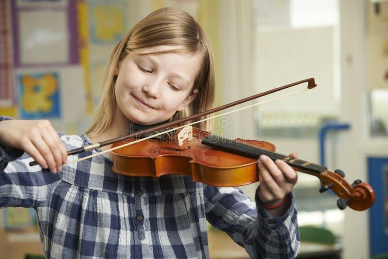 Flicka som lär att spela fiolen i skolamusikkurs royaltyfria bilder