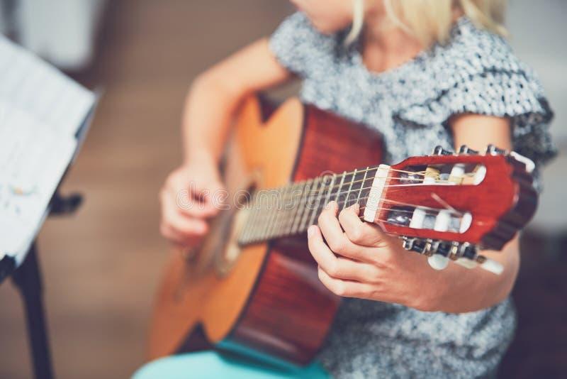 Flicka som lär att spela till gitarren arkivbild