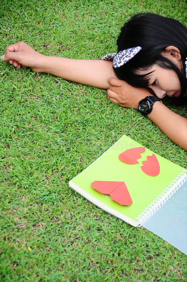 Flicka som läser boken av hjärta på gräs arkivbilder