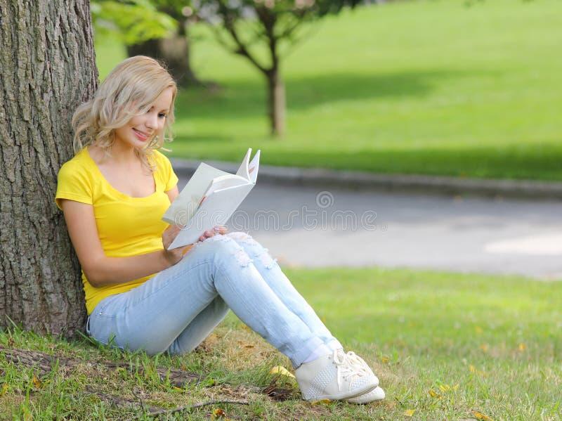 Flicka som läser boken. Blond härlig ung kvinna med boksammanträde på gräset och benägenhet till trädet. Utomhus-. royaltyfri fotografi