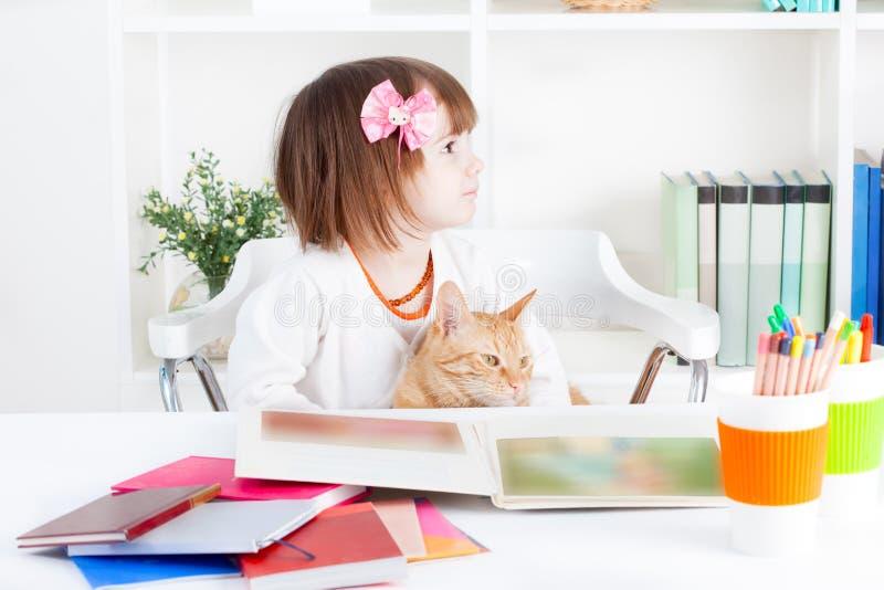 Flicka som läser en bilderbok med hennes katt royaltyfri foto