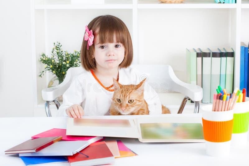 Flicka som läser en bilderbok med hennes katt royaltyfria bilder