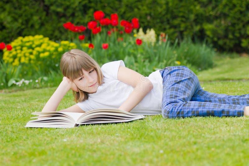Flicka som läser en bok i en trädgård arkivfoton