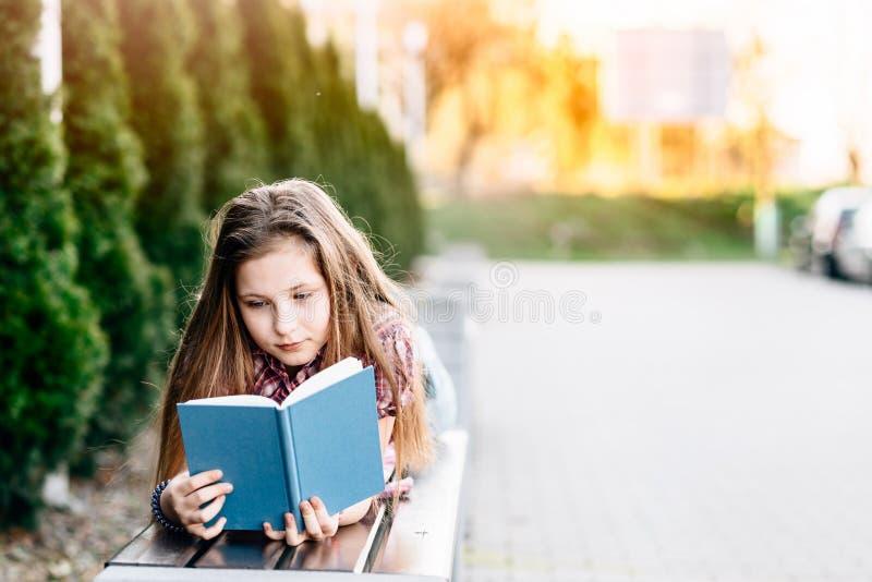 Flicka som läser en bok, medan ligga på bänken i parkera arkivbild