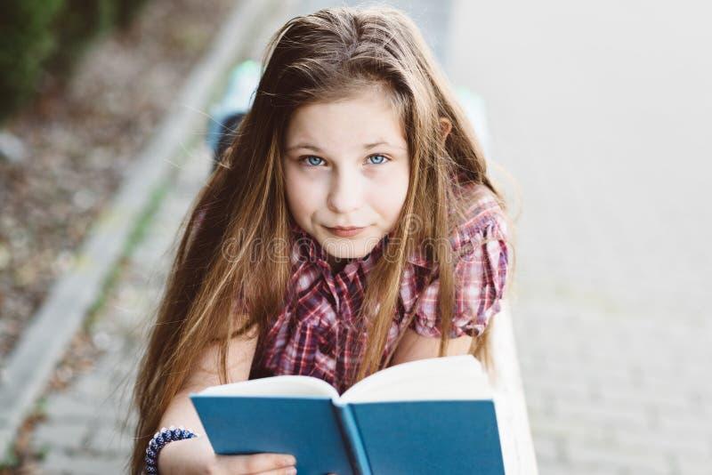 Flicka som läser en bok, medan ligga på bänken i parkera royaltyfria bilder