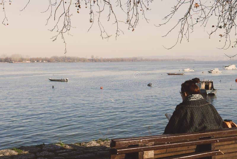 Flicka som läser en bok och tycker om i soligt väder vid floden royaltyfri bild