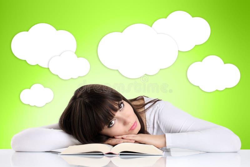 Flicka som läser en bok som vilar på en grön bakgrund med moln fotografering för bildbyråer