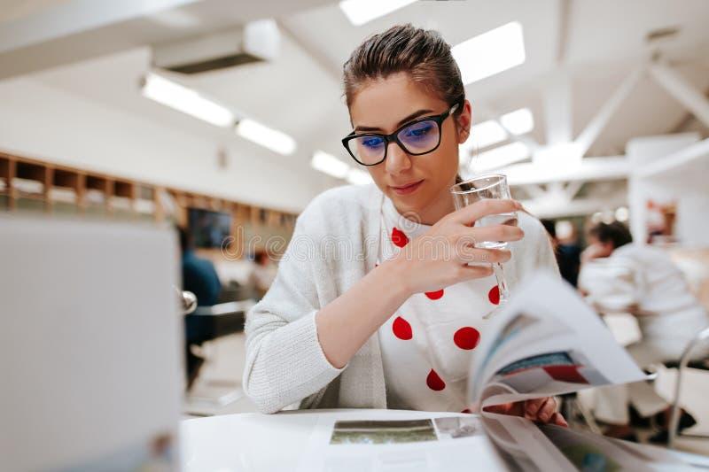 Flicka som läser en tidskrift royaltyfria bilder