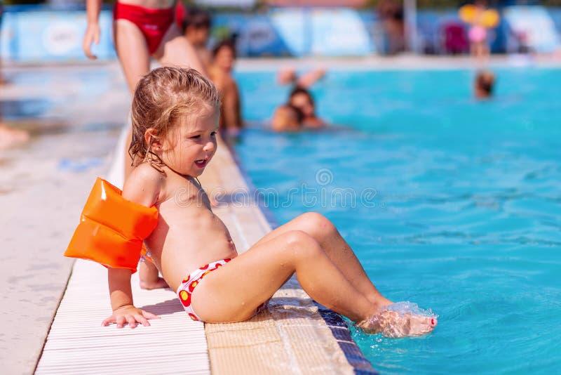 Flicka som l?rer att simma Ungar i simbass?ng royaltyfri bild