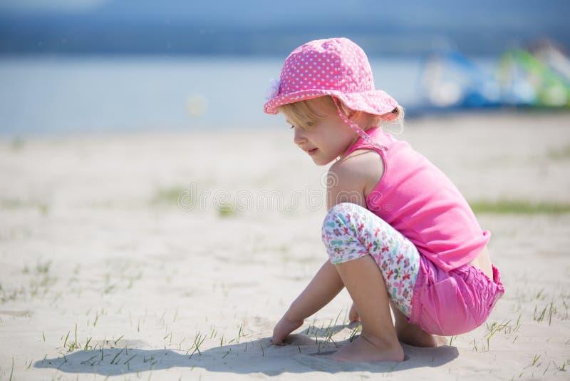Flicka som leker med sanden arkivfoton
