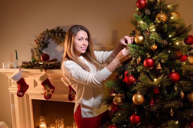 Flicka som ler för en bild som dekorerar trädet för nytt år royaltyfri fotografi