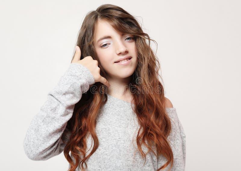 Flicka som ler göra telefongest med handen och fingrar som samtal på telefonen Meddelande begrepp arkivfoton