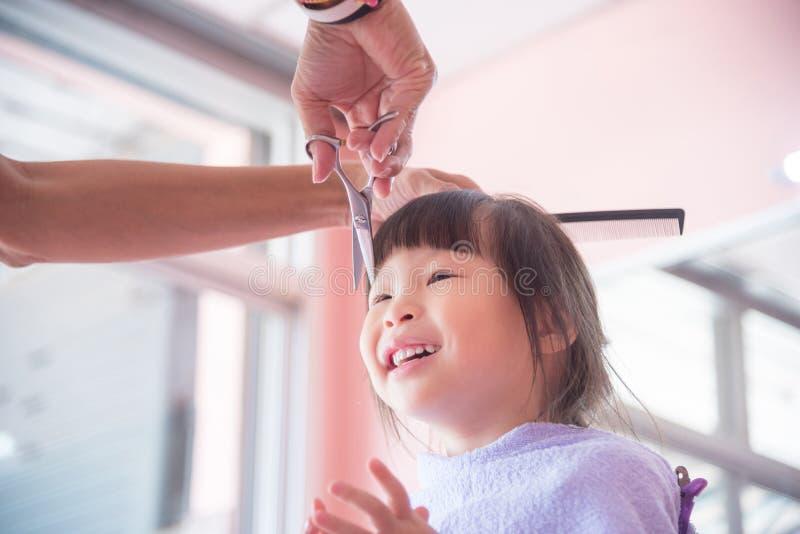 Flicka som ler medan frisör som klipper hennes hår arkivbilder