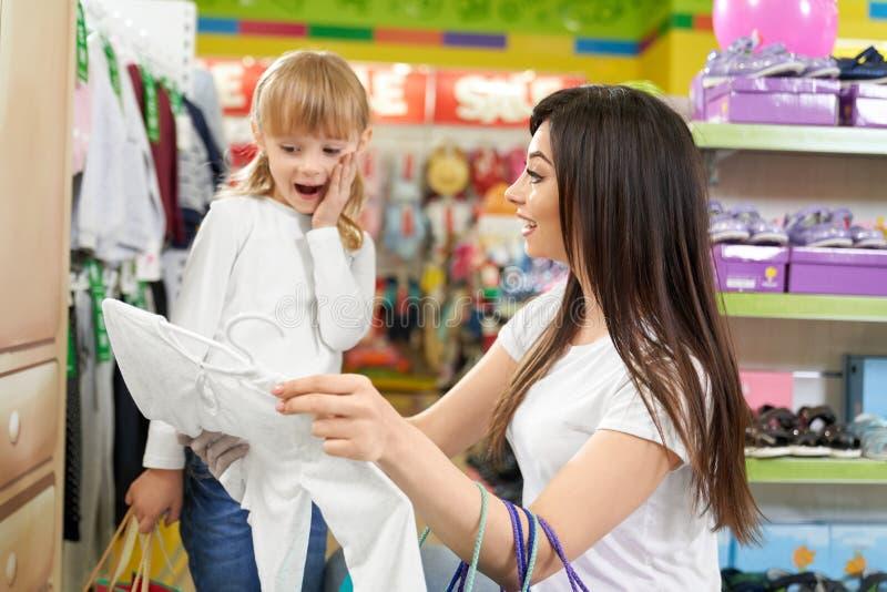 Flicka som ler och ser ny kläder i stort lager royaltyfri bild
