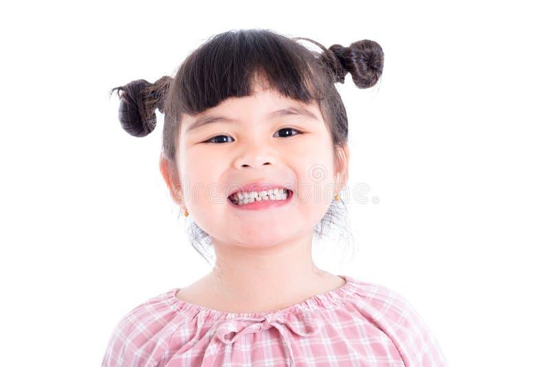 Flicka som ler och visar hennes tänder över vit bakgrund arkivfoton