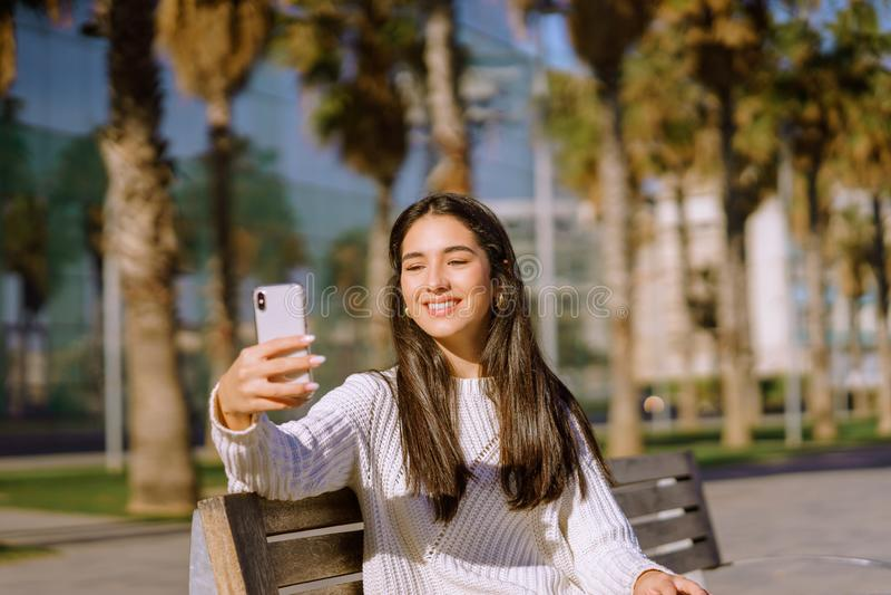 Flicka som ler på kameran genom att använda en telefon för att göra en selfie - bild fotografering för bildbyråer