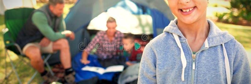 Flicka som ler på kameran medan familjsammanträde på tältet i bakgrund royaltyfria bilder