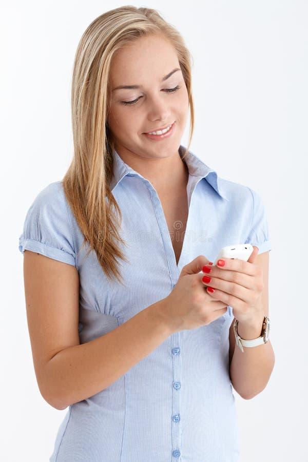flicka som ler tonårs- texting arkivbilder