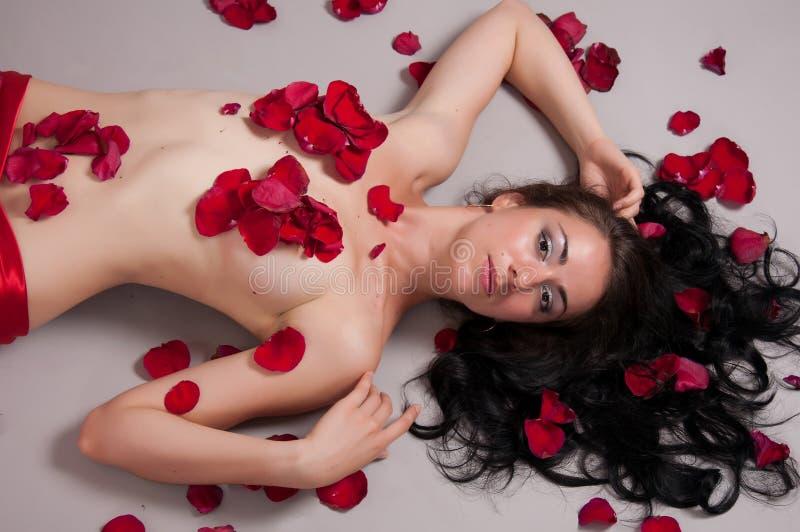 Flicka som ligger i rosa kronblad  arkivfoton