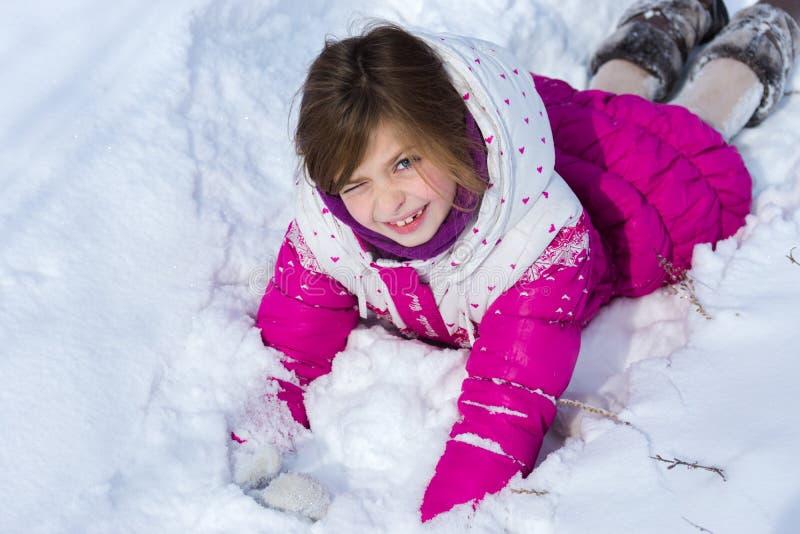 Flicka som ligger i snowen arkivfoton