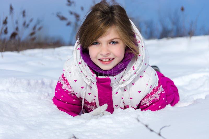 Flicka som ligger i snowen arkivbilder