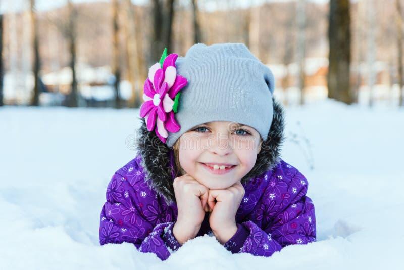 Flicka som ligger i snowen royaltyfria bilder