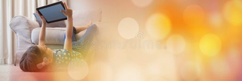 Flicka som ligger med minnestavlan i luft och gulingbokehövergång royaltyfria bilder