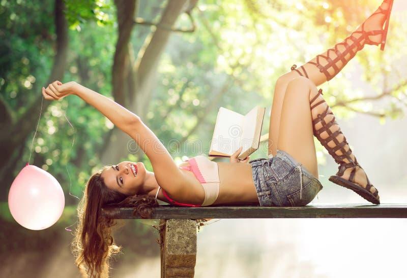 Flicka som ligger på bänk med boken och ballongen royaltyfri fotografi
